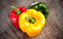 Colored bell peppers on wooden table